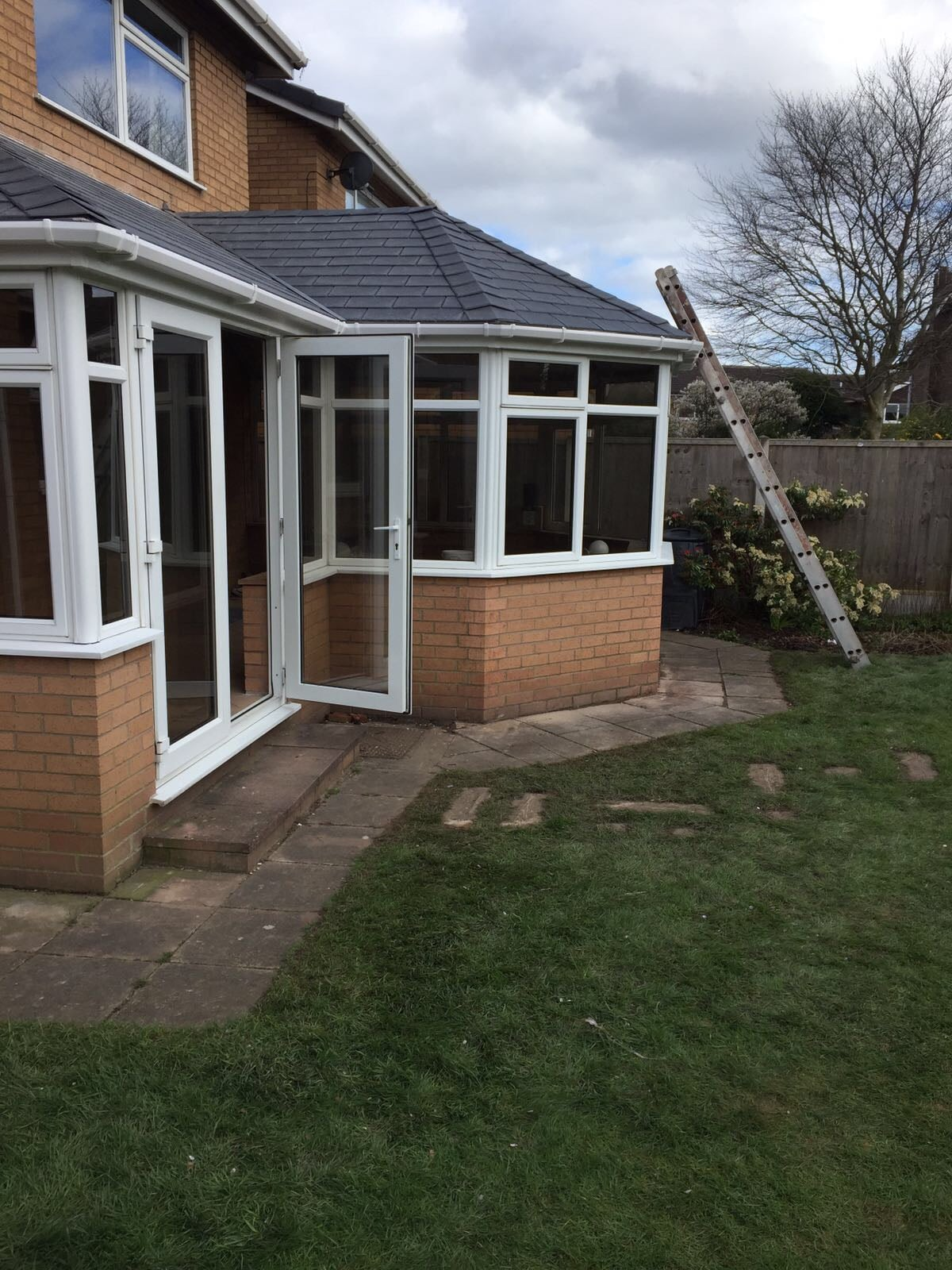 back of house conservatory with ladder on roof